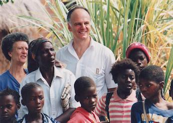 David Nabarro standing in a group of children and a few adults in Mozambique.