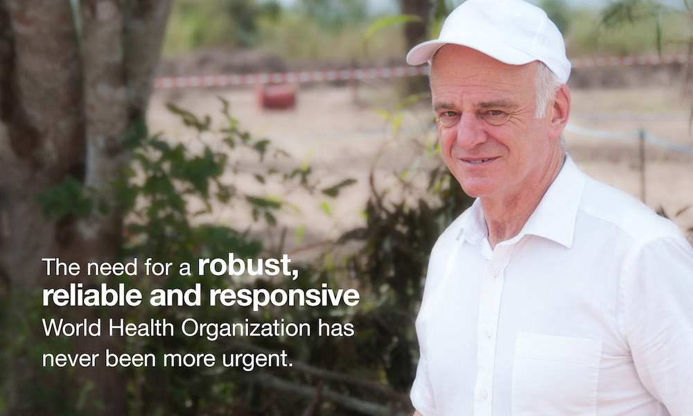 David Nabarro on airfield in Guinea. Text on image: The need for a robust, reliable and responsive World Health Organization has never been more urgent.